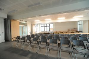 Photo shows rows of chairs in conference room with tables behind and door to garden