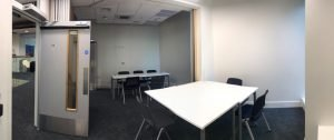 Panoramic photo showing entrance door on left and wide view of 2 spaces with tables